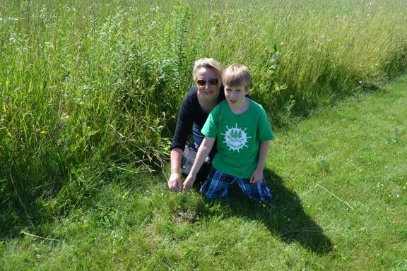Executive Director Andrea Koehle Jones checks-up on seedlings planted by campers.